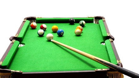 Miniature billiards table with cue and balls on white background photo
