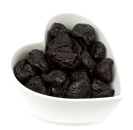 Prunes in a heart shaped bowl isolated on white background photo