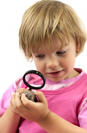 Girl with magnifying glass studying a rock photo