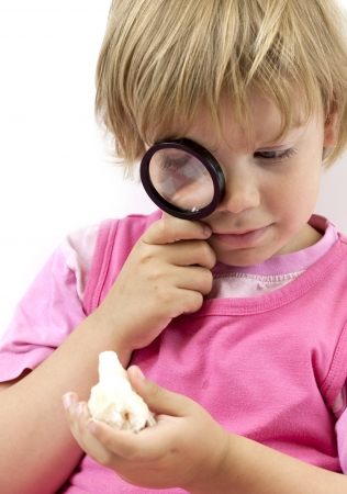 Girl with magnifying glass on white background photo