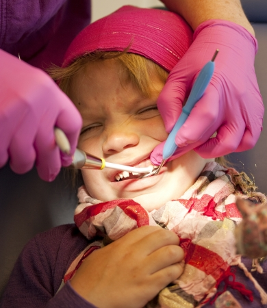 Little girl getting her teeth checked at the dentist photo
