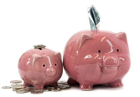 larger: Small and larger piggy banks with coins and notes