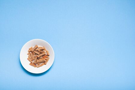 Brown roasted dry bread sticks croutons on white plate with copy space isolated on blue background