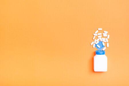 White pills spilling out of pill bottle on orange background