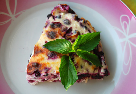 Eaten Cheesecake with bluberries and fresh peppermint leaves on top on a plate. A simple homemade recipe for beginners confectioners.