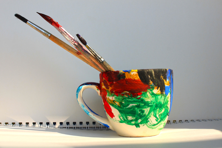 Art brushes in a painted cup on the white background, copy space, bright colours.