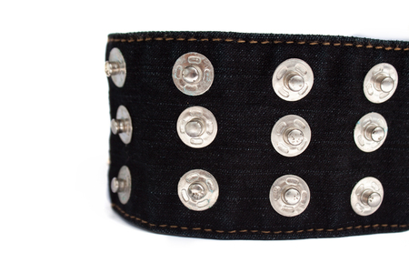 Macro picture of black jeans belt with many buttons isolated on a white background, copy space. Rock music, alternative punk fashion.