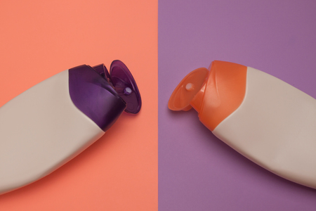 Two opened cosmetic packaging bottles, containers. Beauty products, shower, decorative cosmetics. Peach and purple colors background, flat lay, top view, minimalistic pop-art style, branding mock up. Zdjęcie Seryjne