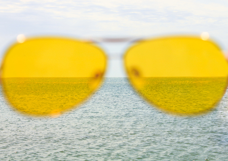 Yellow sunglasses on the sea water and blue sky background. Sunny day, happy vacation, good rest, happiness. Summer view of the sea through the glasses. Stock Photo