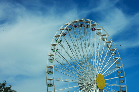 Multicolour ferris wheel on blue sky background, sunny summer weather, bright sun, happy day. Copy space, street photography. Stock Photo