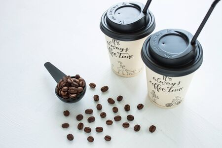 Kraft paper coffee cup with black lid and tubule from street shop with a spoon of coffee beans on light background. Lifestyle concept, take away drinks. Copy space, front view.