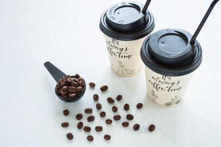 Taza de café de papel kraft con tapa negra y túbulo de street shop con una cuchara de granos de café sobre fondo claro. Concepto de estilo de vida, bebidas para llevar. Copie el espacio, vista frontal.