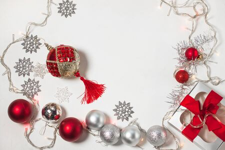 Christmas composition of red and silver decorations and gift box on a white background. Foto de archivo