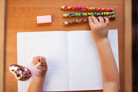 A child holds a pen in the left hand and writes in an empty notebook on a wooden desk. Stationery, colour pencils and eraser. Back to school concept. Top view, copy space.
