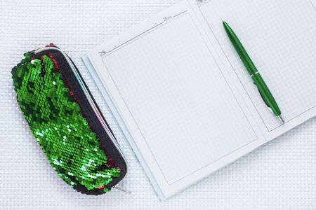 Opened notebook, fashion pencil case with sequins and green pen on white textured background. Minimal work space, stylish stationery, office tools, working and educational supplies. Top view,flat lay. Stok Fotoğraf