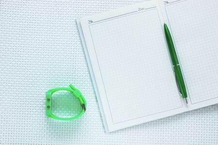 Opened notebook, fashion wrist watch and green pen on white textured background. Minimal work space, stylish stationery, office tools, working and educational supplies. Top view , flat lay.