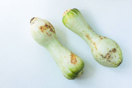 Ugly food concept. Unusual shaped zucchini with mold, scar-like structure, scratches. Organic deformed green courgette vegetable on a white background. Copy space, top view, flatlay,minimalistic style 版權商用圖片