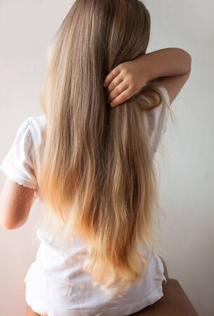 Cute girl with long blond hair. Back view of little girlie looking on side. Isolated on light background.