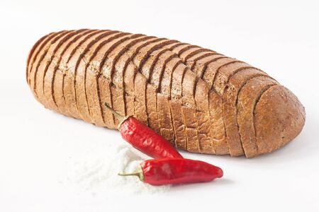 Rye bread with red chili peppers and salt on a white background isolated. Chopped bakery products made with various flours from grain. A loaf sliced into pieces, breakfast toast. Copy space,wallpaper.