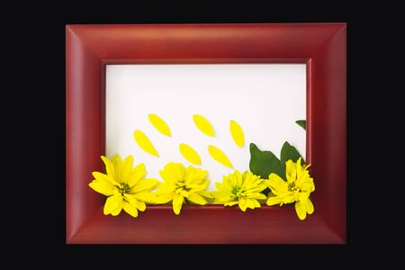 Wooden photo frame with yellow flowers on a black background. Hello autumn card. Home interior decor, mockup, space for text. Beautiful nature, vintage colors, minimal style concept.