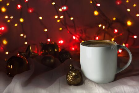 Christmas coffee cup with new year decorations on background. Winter holidays card, cozy home concept, festive wallpaper. White mug with hot drink. Copy space with bokeh lights. Stok Fotoğraf