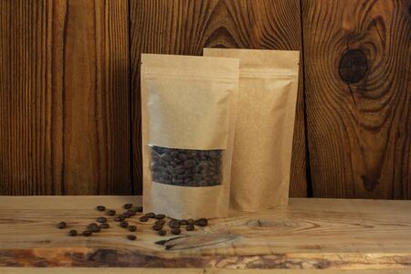 Brown kraft paper pouch bags with coffee beans front view on a wooden background. Packaging for foods and goods template mock-up. Packs with clasps and windows for tea leaves and weight products.