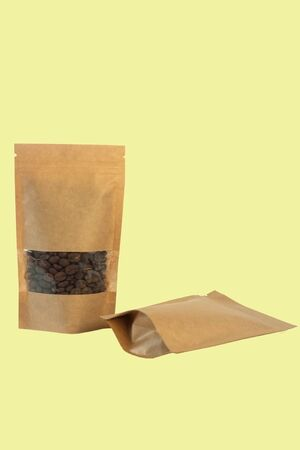 Brown kraft paper pouch bags with coffee beans front view on a yellow background. Packaging for foods and goods template mock-up. Packs with clasps and windows for tea leaves and weight products. Banco de Imagens