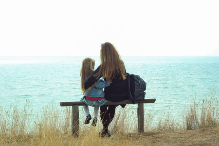 Family travel. Mom and daughter are sitting together on a wooden bench and hugging. Stock Photo