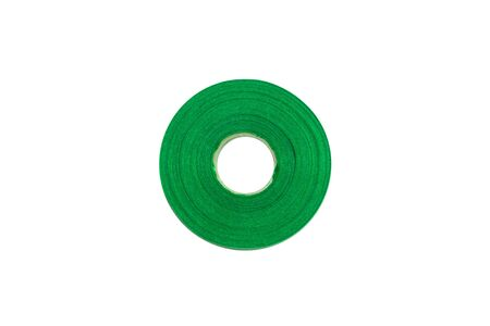Green shiny floristic ribbon in a roll on a white background isolated. Art materials for gifts and flowers bouquets packaging. Accessories for hand-made and sewing shops. Copy space, flatlay.