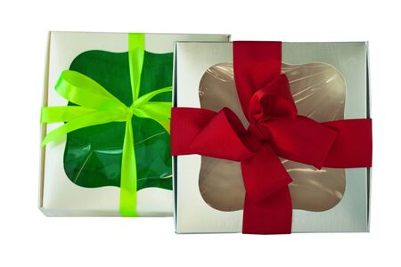Beige and silver gift boxes with a red and green ribbon bows isolated on a white background. Packaging with a transparent window.Holidays, Christmas, Valentines day presents, birthday party.Copy space