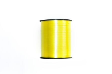 Yellow shiny floristic ribbon in a bobbin on a white background isolated. Art materials for gifts and flowers bouquets packaging. Accessories for hand-made and sewing shops. Copy space, flatlay.