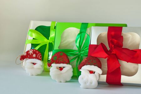 Gift boxes with a Santa decorations and ribbon bows isolated on a white background. Packaging with a transparent window. Holidays, Christmas, New year presents, birthday party. Copy space