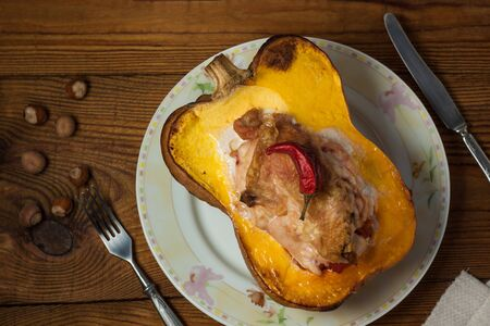 Stuffed pumpkin top view, flatlay. Halloween concept. Squash half with chicken breast, hazelnuts and red pepper on a wooden background. Spicy main dish, vegetables and meat.Food photography.Copy space