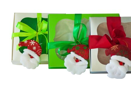 Gift boxes with a Santa decorations and ribbon bows isolated on a white background. Packaging with a transparent window. Holidays, Christmas, New year. Copy space, advertising banner for website. Stock Photo