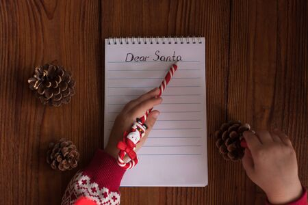 Dear Santa letter, Christmas card. Cute young kid wearing a sweater, holding a pen and writting on a white sheet on a wooden background with pine cones.Childhood dreams about gifts.New year concept.