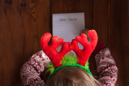 Dear Santa letter, Christmas card. Cute young girl wearing deer horns, holding a pen and writting on a white sheet on a wooden background with pine cones.Childhood dreams about gifts.New year concept.