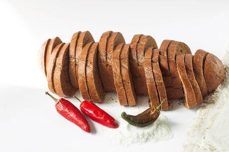 Rye bread with red chili peppers and salt on a white background isolated. Chopped bakery products made with various flours from grain. A loaf sliced into pieces, breakfast toast. Kitchen wallpaper.