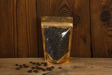 Golden metallized pouch bag with coffee beans front view on a wooden background. Packaging for foods and goods template mock-up. Foil packs with windows and clasps for tea leaves and weight products.