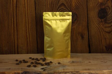 Golden metallized pouch bag with coffee beans front view on a wooden background. Packaging for foods and goods template mock-up. Foil packs with clasps for tea leaves and weight products. Stock Photo