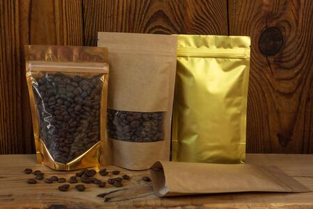 Brown kraft paper and golden metallized pouch bags with coffee beans front view on a wooden background. Packaging for foods and goods template mock-up. Packs with windows for weight products.