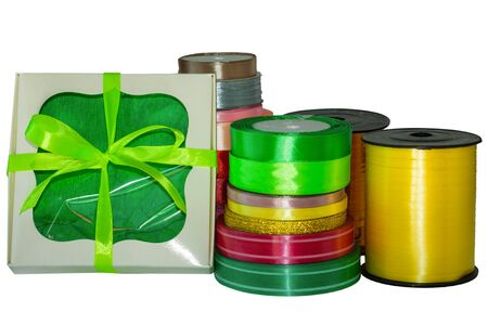 Gift boxes and colorful shiny floristic ribbons in a bobbins on a white background isolated. Art materials for presents, flowers bouquets packaging. Accessories for hand-made sewing shops. Copy space.