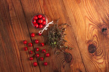 Immunity boosting treatments. Natural thyme, mint herbs and rosehip berries in a jar on a wooden background. Phyto therapy remedies, healthcare infusions.Cold and flu medicine,ethnoscience,homeopathy. Stockfoto