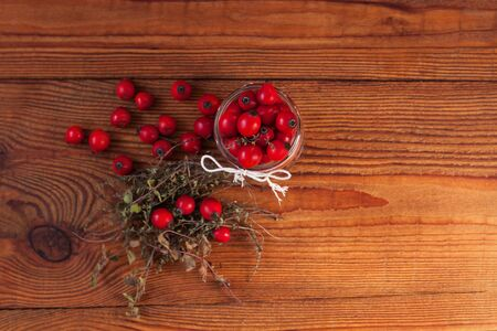 Immunity boosting treatments. Natural thyme, mint herbs and rosehip berries in a jar on a wooden background. Phyto therapy remedies, healthcare infusions.Cold and flu medicine,ethnoscience,homeopathy. Stock Photo