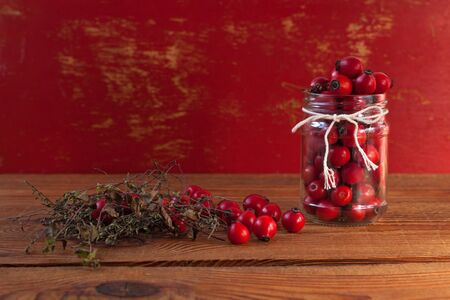 Immunity boosting treatments. Natural thyme, mint herbs and rosehip berries in a jar on a wooden background. Phyto therapy remedies, healthcare infusions. Cold and flu medicine, ethnoscience, homeopathy. Фото со стока