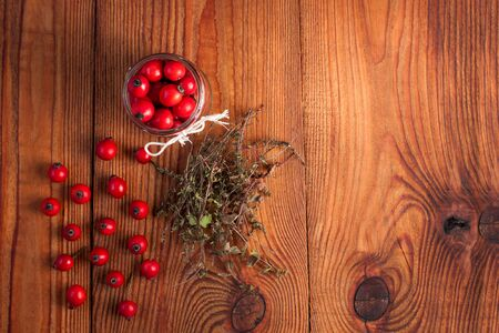 Immunity boosting treatments. Natural thyme, mint herbs and rosehip berries in a jar on a wooden background. Phyto therapy remedies, healthcare infusions.Cold and flu medicine,ethnoscience,homeopathy. Фото со стока
