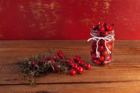 Immunity boosting treatments. Natural thyme, mint herbs and rosehip berries in a jar on a wooden background. Phyto therapy remedies, healthcare infusions. Cold and flu medicine, ethnoscience, homeopathy. Stock Photo