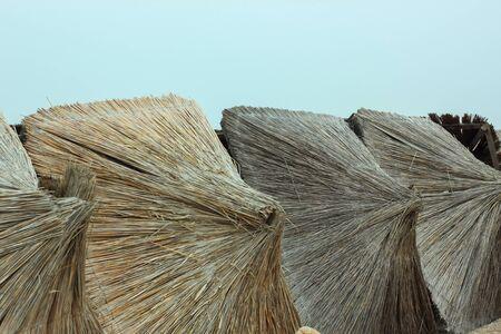 Straw umbrellas on an empty beach on a foggy day. Rainy cold weather on the sea coast. Travel photography. Stok Fotoğraf