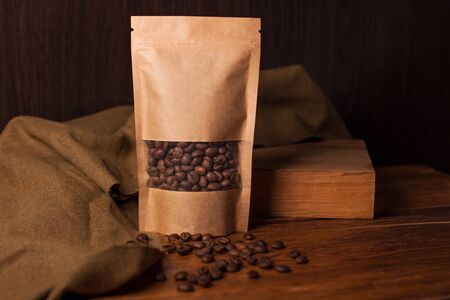 Blank brown kraft paper pouch bag with coffee beans in transparent window on wooden background. Trendy packaging for tea