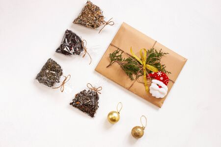 New year flat lay. Christmas tea gift box wrapped in kraft paper with pine tree cones.Mockup template. Winter holidays