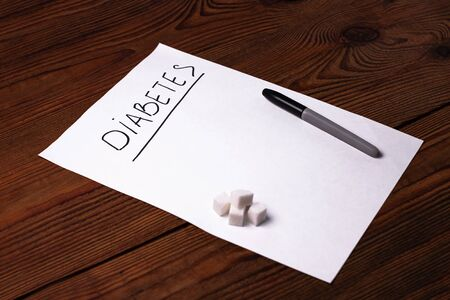Stop Diabetes sign on a white paper sheet with sugar cubes on wooden background, World diabetes day November 14. Prevent disease before it begins,detection diagnosis, clinical researches,patients list